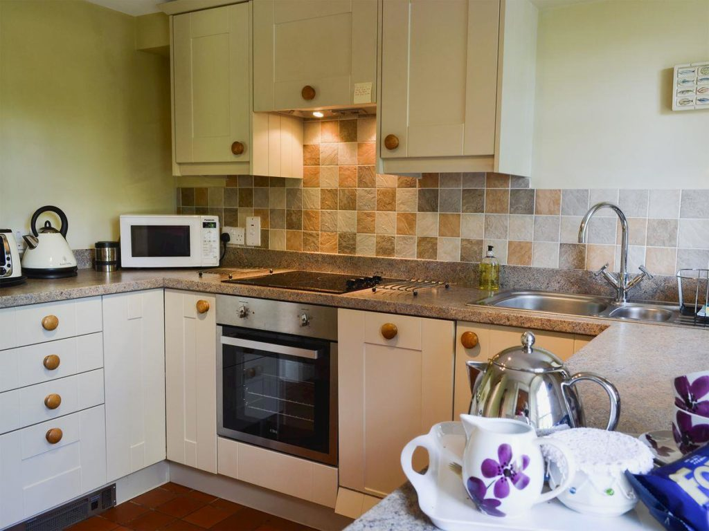 Well equipped bespoke kitchen with washing machine, dishwasher, microwave and fridge freezer